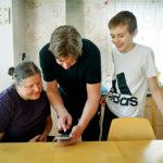 Linda, Magnus och Vilhelm Funcke tittar på filmen från uppträdandet.